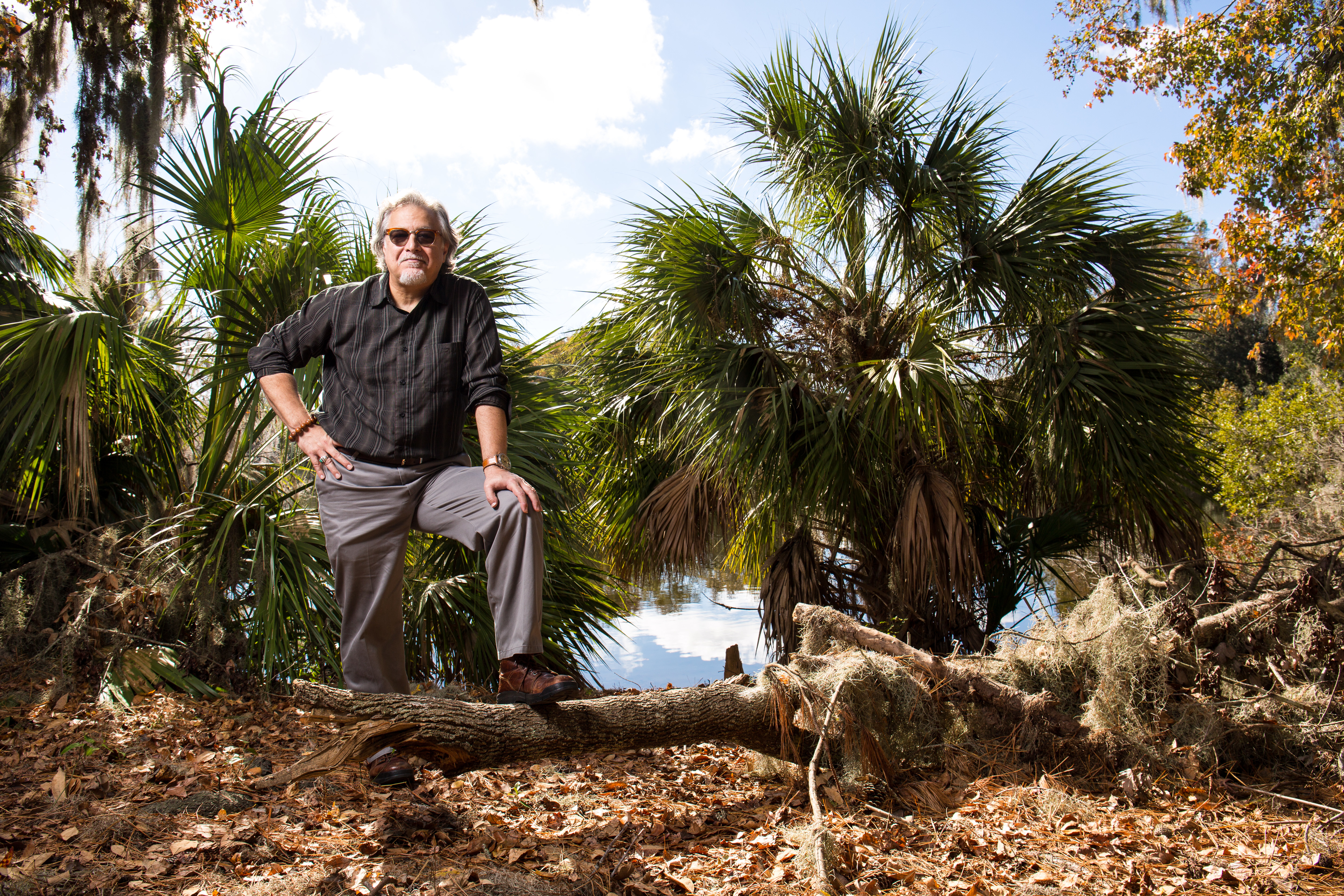 Thomas Bianchi stands on a fallen tree by Lake Alice
