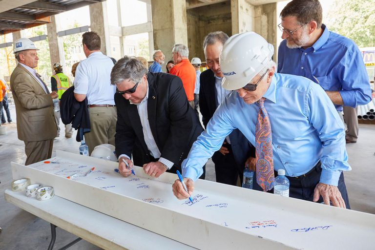 a group of men signing the beam
