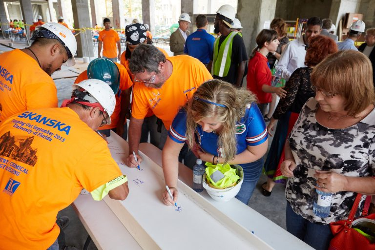 men in hard hats and two women sign the beam