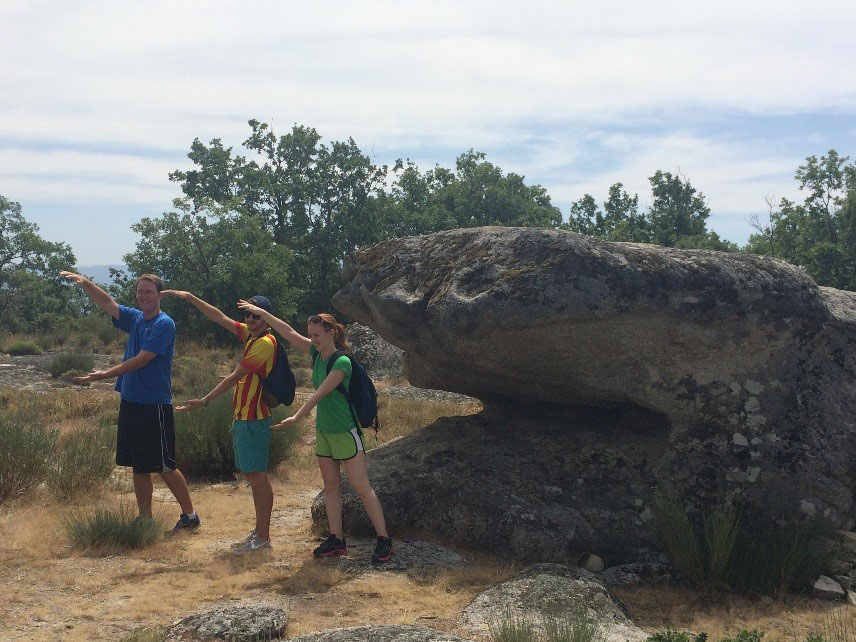 Hikers do Gator Chomp by large rock