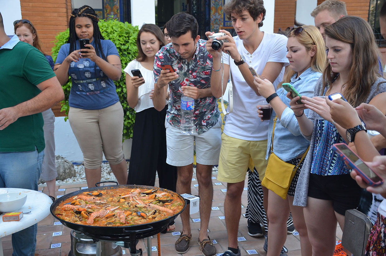UF students in Seville admiring a paella
