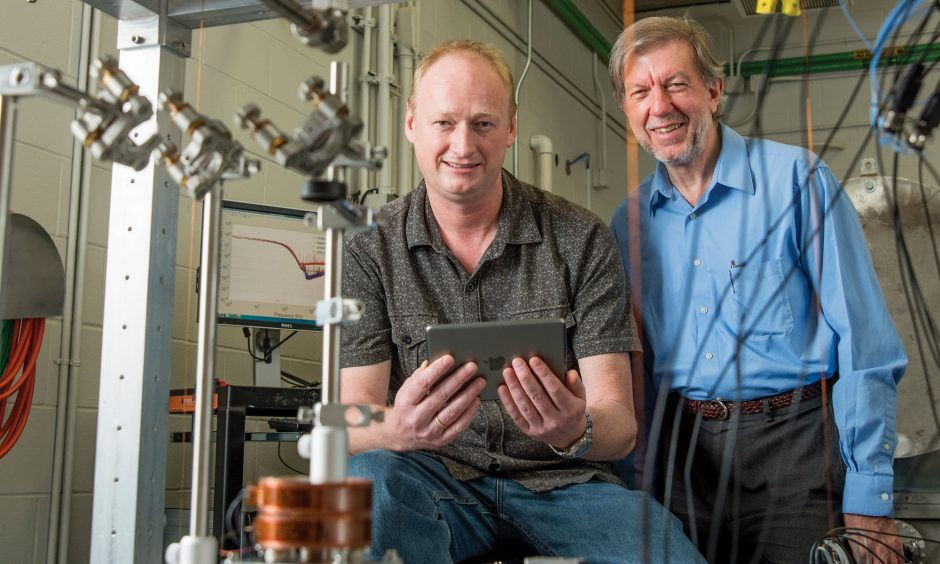 Professors Guido Mueller and Bernard Whiting with a scaled-down version of the LIGO optics.