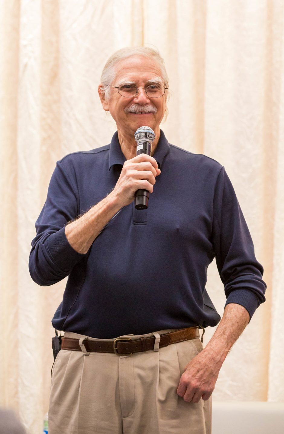 friendly older man holds mic while smiling