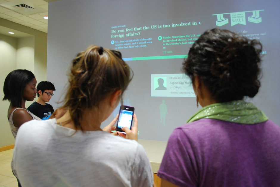 students use devices to engage with survey displayed on large screen in front of them