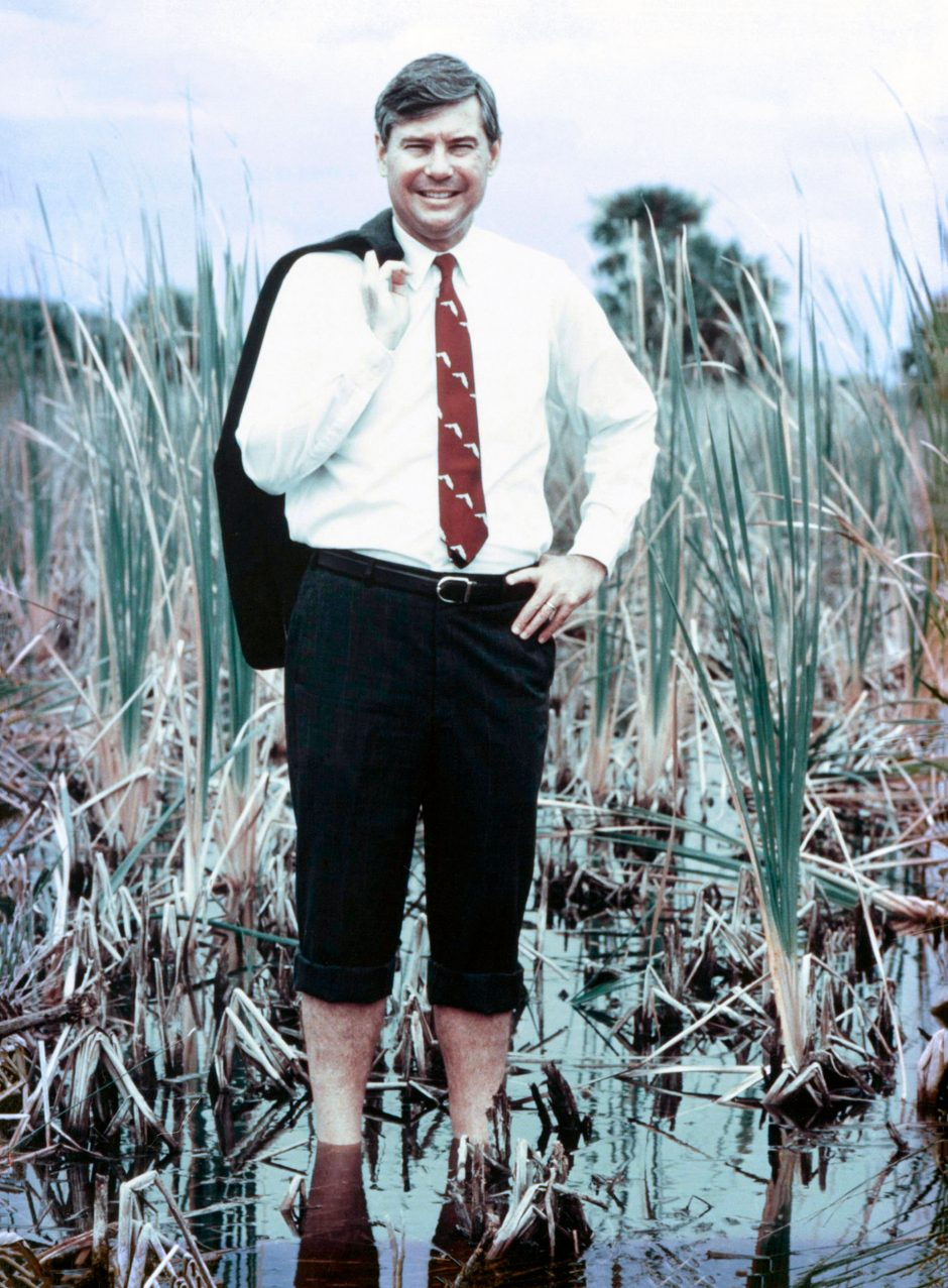 well-dressed man stands in calf-deep in swamp with jacket over shoulder and pants rolled up
