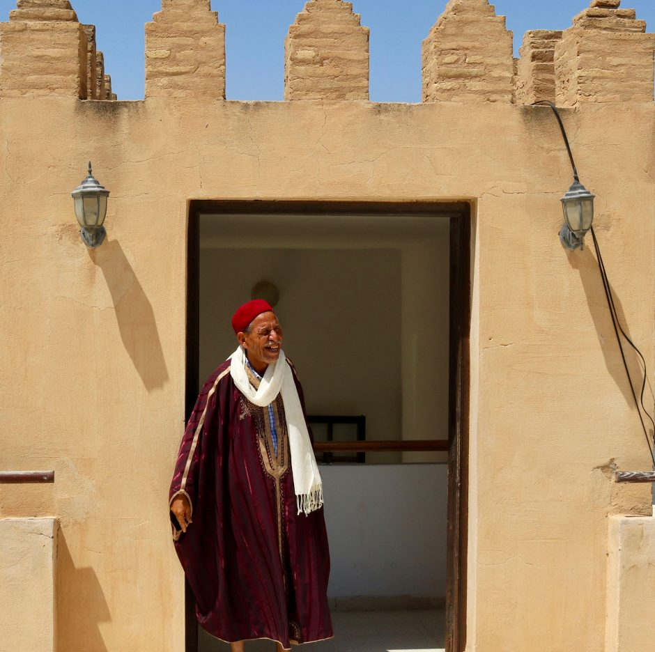 grinning man in traditional attire exits doorway of mosque