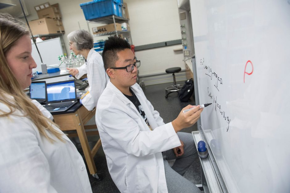 young male student in white coat writes equations on whiteboard