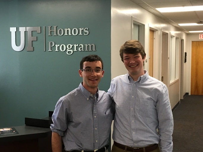 """photo of two smiling young men standing in front of green wall with insigna reading """"Honors Program"""""""