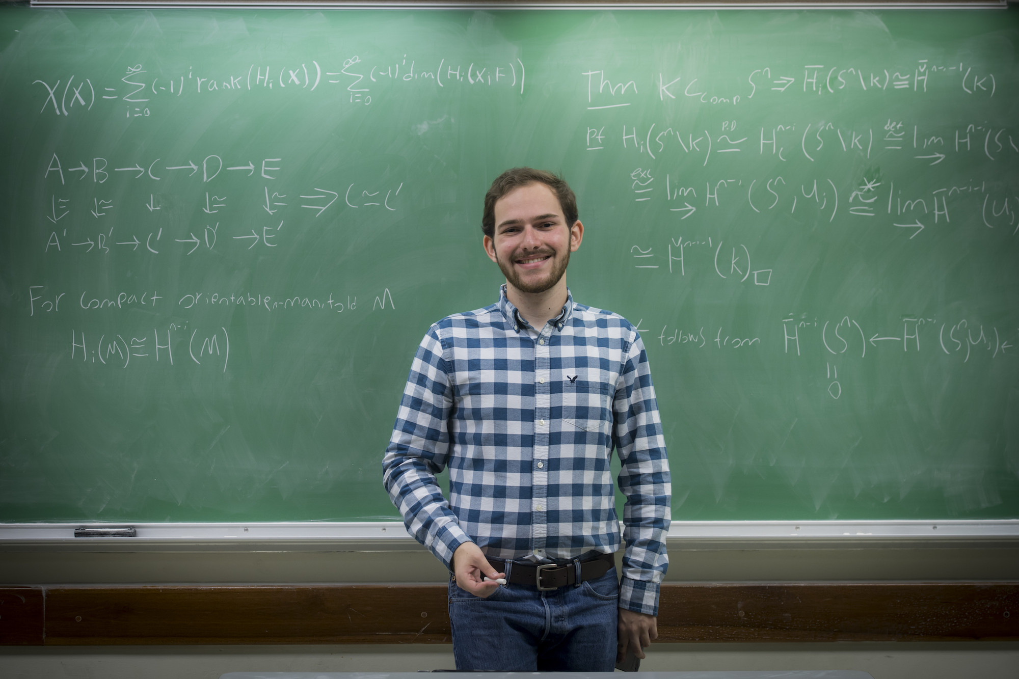 young man standing in front of green chalkboard with math equations