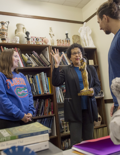 two students excitedly engage with Mary Ann Eaverly, who is holding an Egyptian statue