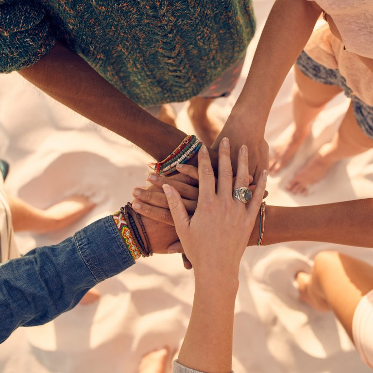 Group of young men and women showing unity. Group of young friends putting their hands together at the beach