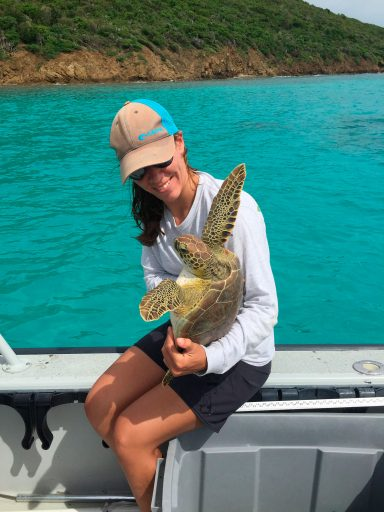 young woman sits on edge of boat holding green turtle with its flippers in the air like it just don't care