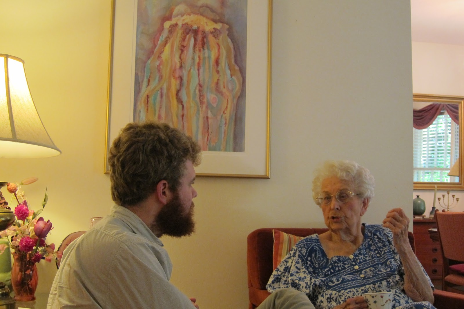 Male interviewing older woman at her home
